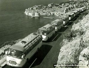 Tourist buses move slowly in a column along the road above Dubrovnik (1960s)