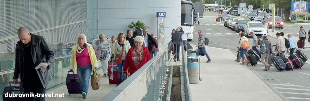 Passengers in Dubrovnik airport with luggage in early autumn