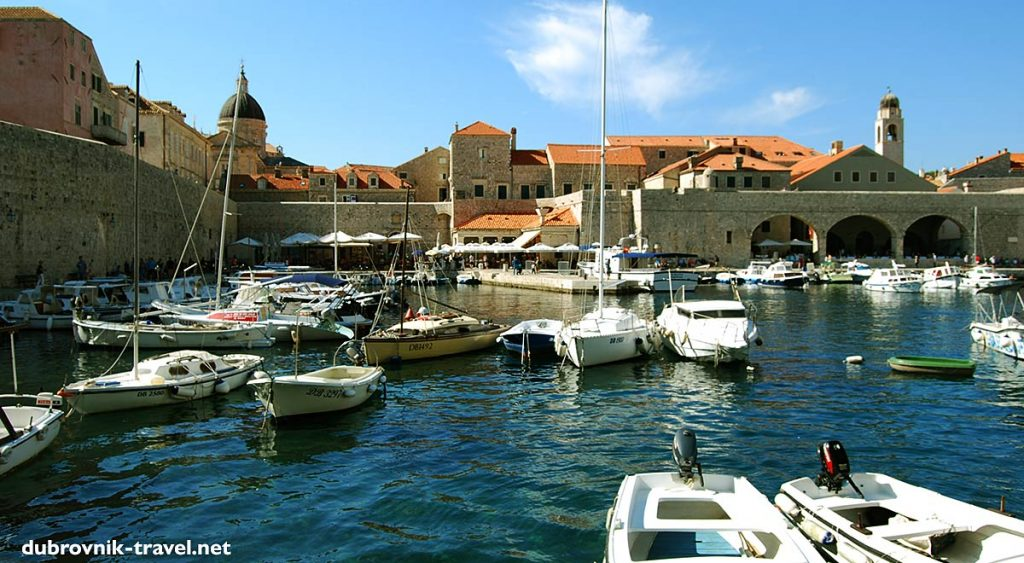Views over old Port of Dubrovnik, the Clocktower and Cathedral with lovely boats and sailing boats in the foreground